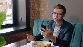 Stående av succesfullaffärsmannen som ser till skärmen av hans smartphone och talar under frukosten i kafé lager videofilmer