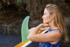 Stående av surfareflickan med surfingbrädan på havsklippabakgrund royaltyfria bilder
