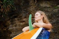 Stående av surfareflickan med surfingbrädan på havsklippabakgrund arkivfoto