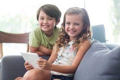 Stående av syskon med digitalt minnestavlasammanträde på soffan i vardagsrum arkivbild