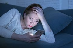 Stående av 30-tal för ung kvinna som sent ligger på sängsoffan på hemmastatt användande socialt massmedia app för natt på den söm royaltyfria foton