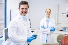 Stående av tandläkaren som rymmer den digitala minnestavlan medan hans kollega i bakgrund royaltyfri bild