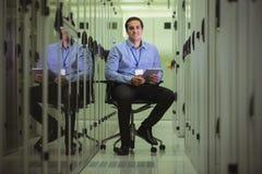 Stående av teknikeren som placerar på stol och använder den digitala minnestavlan Arkivbild