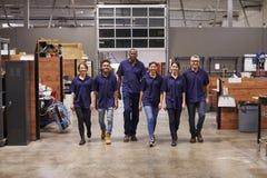 Stående av teknikerer och lärlingar i upptagen fabrik Arkivfoton