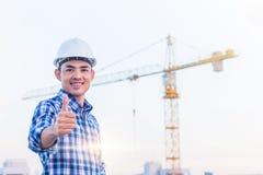Stående av teknikern att bära en vit säkerhetshjälm på konstruktionsplatsen med kranbakgrund Han har leende, d?rf?r att hans proj arkivbild