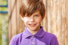 Stående av tio år gammal pojke i purpurfärgad poloskjorta Royaltyfria Bilder