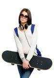 Stående av tonåringen med skateboarden, hörlurar och ryggsäcken Arkivfoton