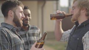 Stående av tre caucasian- och afrikansk amerikanmän som utomhus dricker öl Gamla vänner har gyckel tillsammans lager videofilmer