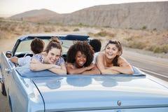 Stående av tre kvinnliga vänner som tycker om vägtur i öppen bästa klassisk bil arkivbild