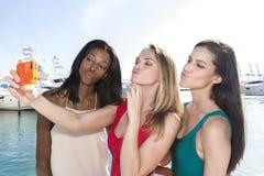 Stående av tre kvinnor som tar and-framsida selfies med en smartphone royaltyfri foto