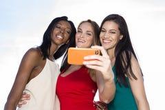 Stående av tre kvinnor som tar selfies med en smartphone arkivbilder