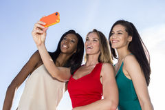 Stående av tre kvinnor som tar selfies med en smartphone royaltyfri foto