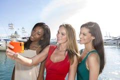 Stående av tre kvinnor som tar selfies med en smartphone royaltyfri fotografi