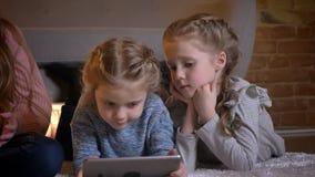 Stående av tre lilla caucasian flickor som ligger på golvet och håller ögonen på in i minnestavlan med uppmärksamhet i mysigt hem stock video