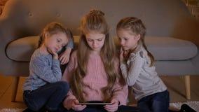 Stående av tre nätta caucasian flickor som sitter på golvet och uppmärksamt håller ögonen på in i minnestavlan i mysigt hem stock video