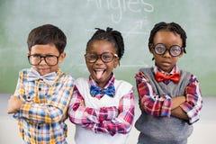 Stående av tre skolaungar som står mot den svart tavlan Fotografering för Bildbyråer