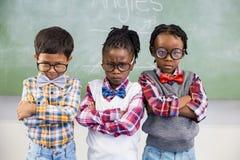 Stående av tre skolaungar som står mot den svart tavlan Royaltyfri Bild