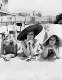 Stående av tre unga kvinnor som ligger på stranden (alla visade personer inte är längre uppehälle, och inget gods finns Leverantö Arkivbilder