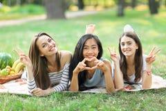 Stående av tre unga kvinnor som visar teckenfred och hjärta Royaltyfri Foto
