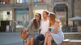 Stående av två attraktiva flickor och den stiliga pojken med lockigt hår som tar Selfie genom att använda Smartphone och pinnen t arkivfilmer