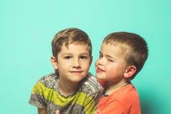 Stående av två barn på en blå bakgrund arkivbild