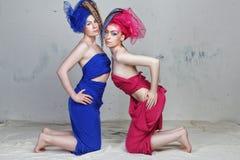Stående av två flickvänner: flickor med dreadlocks i groteska klänningar av blått och rött är på deras knä Royaltyfria Foton