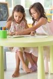 Stående av två gulliga små flickor som tillsammans drar fotografering för bildbyråer