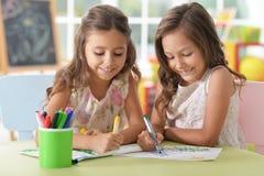 Stående av två gulliga små flickor som tillsammans drar arkivbilder