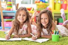 Stående av två gulliga små flickor som tillsammans drar royaltyfri bild
