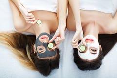 Stående av två härliga flickor med ansiktsbehandlingkräm på deras framsidor arkivbilder