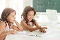 Stående av två härliga små flickor med bärbara datorn royaltyfri bild