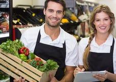 Stående av två kollegor som rymmer en ask med nya grönsaker och skriver på notepaden Arkivfoton