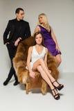 Stående av två kvinnor och män som en bär elegant kläder på svart Arkivfoton