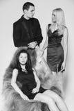 Stående av två kvinnor och män som en bär elegant kläder på svart Fotografering för Bildbyråer