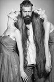 Stående av två kvinnor och män som en bär elegant kläder på svart Skäggig man och två kvinnor Royaltyfria Foton