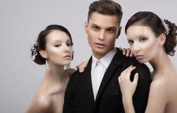 Stående av två kvinnor och män som en bär elegant kläder på svart Två charmiga kvinnor som kramar en stilig man Arkivbild