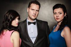 Stående av två kvinnor och män som en bär elegant kläder på svart Två kvinnor och en man sveket Arkivbild