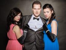Stående av två kvinnor och män som en bär elegant kläder på svart Två kvinnor och en man sveket Fotografering för Bildbyråer