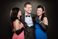 Stående av två kvinnor och män som en bär elegant kläder på svart Två skratta kvinnor och man Gyckel Royaltyfri Fotografi