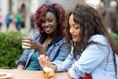 Stående av två kvinnor som tar en drink i en bomma för. Stads- bakgrund royaltyfria foton
