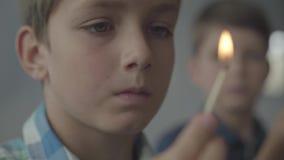Stående av två lilla bröder som spelar med branden i den rökiga rumnärbilden Ungar som ut sätter matcher och att se lager videofilmer