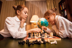 Stående av två lilla systrar som spelar schack Royaltyfria Bilder