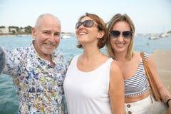 Stående av två lyckliga kvinnor och en äldre man över sjösidapromenad som tar selfie arkivbilder