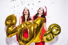 Stående av två lyckliga unga kvinnor i röda klänningar och den santa hatten på partiet med konfettier och 2018 nummer i händer öv Fotografering för Bildbyråer