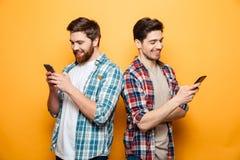 Stående av två lyckliga unga män som använder mobiltelefoner royaltyfri foto