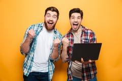 Stående av två lyckliga unga män som rymmer bärbara datorn arkivfoto
