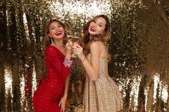 Stående av två nätta le flickor i skinande klänningar Fotografering för Bildbyråer