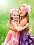Stående av två omfamna gulliga liten flicka royaltyfri bild