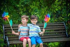 Stående av två pojkar, siblingbröder och le för bästa vän Ungar som sitter på bänklek samman med liten sol utomhus royaltyfri foto