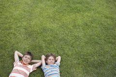 Stående av två pojkar som ligger på gräs royaltyfri fotografi